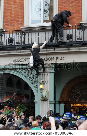 LONDON - MARCH 26: A breakaway group of protesters scale and occupy luxury department store Fortnum and Mason on Piccadilly during a large anti-cuts rally on March 26, 2011 in London, UK.