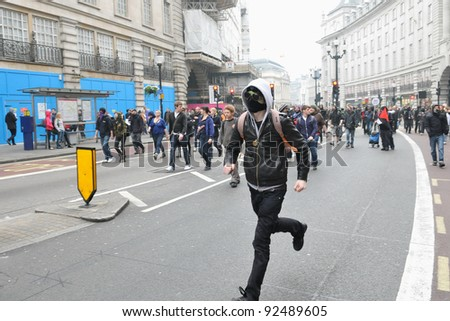 LONDON - MARCH 26: A protester runs along Regent Street during a large anti-cuts rally on March 26, 2011 in London, UK. An estimated 250,000 people took part in the TUC organised rally.