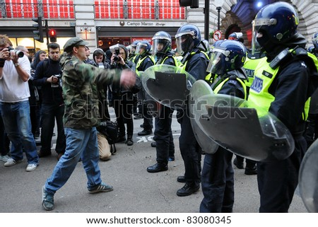 LONDON - MARCH 26: An unidentified protester confronts riot police during a large anti-cuts rally March 26, 2011 in London, UK.