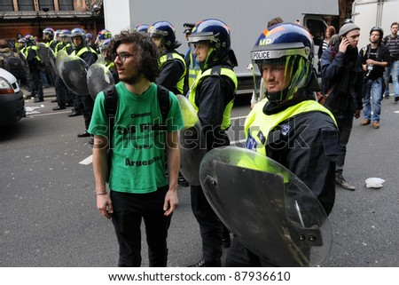LONDON - MARCH 26: An unidentified protester prevented by riot police from passing a cordon during a large TUC organised anti-cuts rally on March 26, 2011 in London, UK.