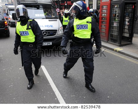 LONDON - MARCH 26: Police in riot gear advance through central London during a large anti-cuts rally on March 26, 2011 in London, UK.