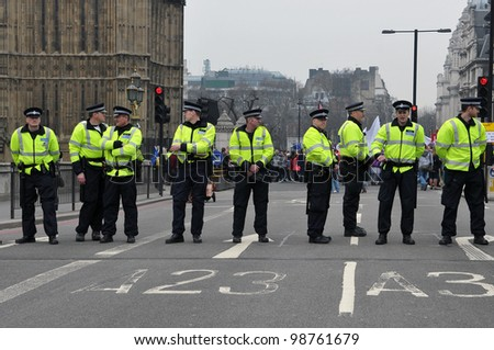 LONDON - MARCH 26: Police stand guard on Westminster Bridge during a large austerity rally on March 26, 2011 in London, UK. Police were on standby after violent clashes with anti-cuts protesters.