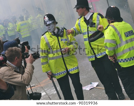 LONDON - MARCH 26: Press photograph police after coming under attack by a breakaway group of protesters during a large anti-cuts rally on March 26, 2011 in London, UK.