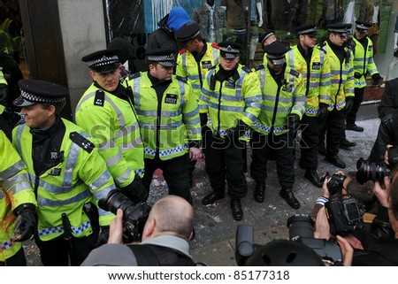 LONDON - MARCH 26: Press photograph police as they form a line to protect a high street shop that came under attack by protesters during a large anti-cuts rally on March 26, 2011 in London, UK. - stock photo