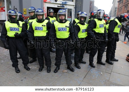 LONDON - MARCH 26: Riot police stand guard outside a branch of HSBC after the bank comes under attack by a breakaway group of protesters during a large anti-cuts rally on March 26, 2011 in London, UK.