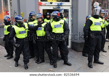 LONDON - MARCH 26: Riot police stand guard outside a branch of HSBC after the bank is vandalised by a breakaway group of protesters during a large anti-cuts rally on March 26, 2011 in London, UK.