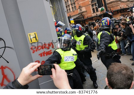 LONDON - MARCH 26: Riot police storm a branch of HSBC after the bank is occupied by a breakaway group of protesters during a large anti-cuts rally on March 26, 2011 in London, UK.