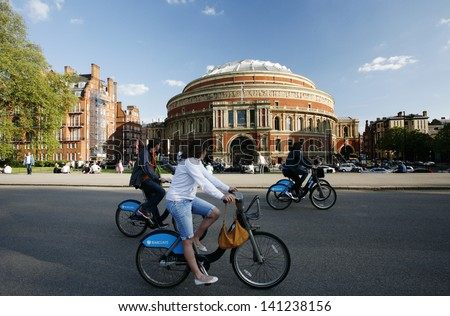 LONDON - MAY 26: Tourists on rental bike passing by Royal Albert Hall on May 26, 2013 in London, UK. London's bicycle sharing scheme launched with 6000 bikes on 2010 to help ease traffic congestion.