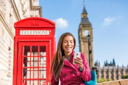 London mobile phone businesswoman walking in the city in stylish pink trench coat, urban lifestyle. Red telephone booth and Big Ben background London, England, UK. Europe travel.