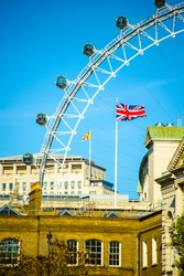 London morning. London eye, County Hall, Westminster Bridge, Big Ben and Houses of Parliament. Flag of Great Britain.