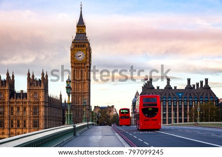 London morning traffic scene with red Double Decker buses move along the Westminster Bridge with Palace of Westminster Elizabeth Tower aka Big Ben in background