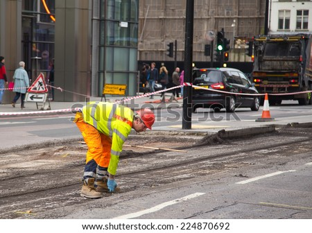 LONDON - OCTOBER 18TH: Unidentified workman resurfacing a road on October 18th, 2014 in London, England, UK. The city council carry\'s out annual road condition surveys