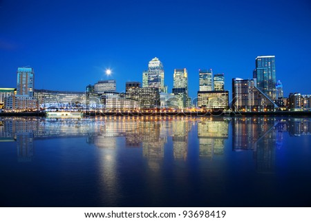London skyscrapers reflected on water at night