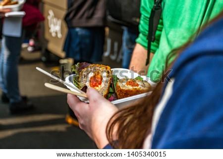 London Street Food Attraction. Girl eats Street Food in London