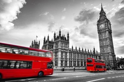 London, the UK. Red buses in motion and Big Ben, the Palace of Westminster. The icons of England in vintage, retro style. Red in black and white