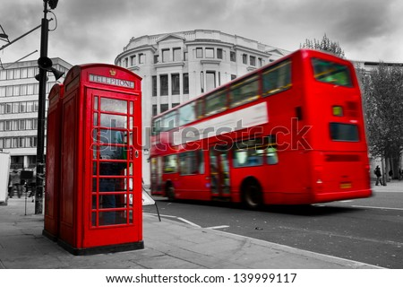 London, the UK. Red phone booth and red bus in motion. English icons