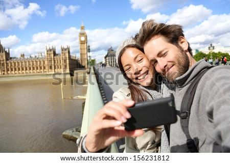 London tourist couple taking photo near Big Ben. Sightseeing woman and man having fun using smartphone camera smiling happy near Palace of Westminster, Westminster Bridge, London, England.
