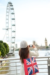 London Tourist taking picture of river Thames with London Eye, Big Ben and Palace of Westminster. Woman holding shopping bag with flag of the United Kingdom, Union Jack and smart phone camera.