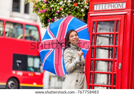 London tourist travel woman with UK flag umbrella, telephone box, red big bus. Europe travel destination Asian girl with british icons, red phonebox, double decker hop on hop off bus in famous city. - Shutterstock ID 767758483