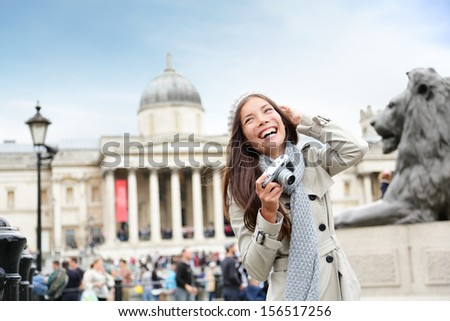 London tourist woman on Trafalgar Square in front of National Gallery taking photo holding camera smiling happy laughing having fun. Beautiful girl on travel vacation, London, England, United Kingdom.