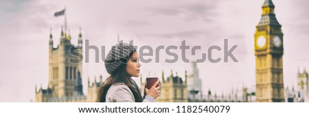 London travel woman drinking coffee cup by Big Ben Westminster in cold morning fall. Asian tourist girl pensive looking at view banner panorama.
