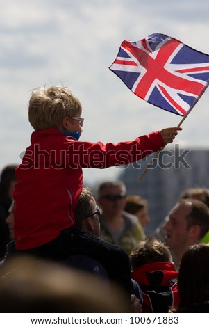 LONDON, UK - APR. 22: A boy waves a union jack flag as tens of thousands of people pass Tower Bridge during the London Marathon on the Apr 22, 2012 in London, UK