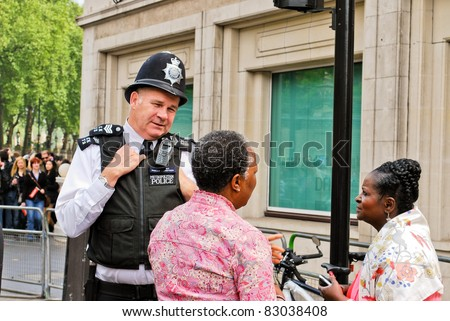 LONDON, UK - APRIL 29: A policeman talking to people at Prince William and Kate Middleton wedding, April 29, 2011 in London, United Kingdom