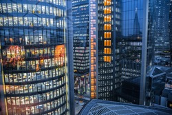 London, UK - 26 April, 2020: City of London windows of office  buildings with lights.