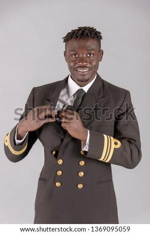London UK. April 2019. Lieutenant Commander wearing uniform of the South African Navy. Putting sunglasses into an inside pocket. Stock fotó ©