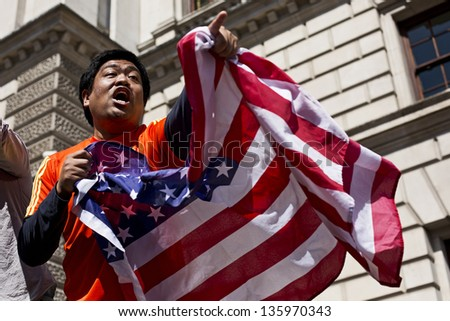 LONDON, UK - APRIL 21: London Marathon spectator waving a flag of United States and cheering to mark Boston bombings on April 21, 2013 in London, UK.