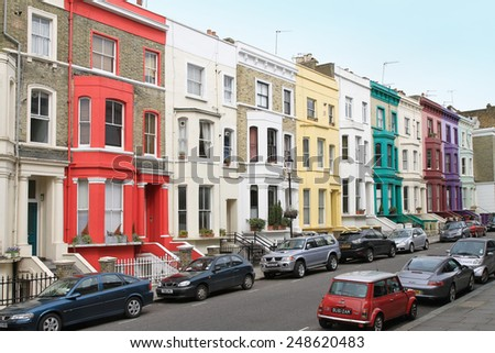 LONDON, UK - April 03: Notting Hill street with colorful houses architecture and parked cars in London, UK - April 03, 2010; Houses with colorful facades in Notting Hill neighborhood
