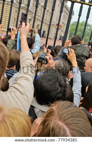 LONDON, UK - APRIL 29: People taking pictures of the first public kiss of Prince William and Kate Middleton at their wedding, April 29, 2011 in front of Buckingham Palace in London, United Kingdom
