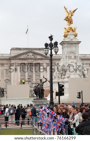 LONDON, UK - APRIL 26: Unidentified girls hold flags of Prince William and Kate Middleton on April 26, 2011 outside Buckingham Palace, London, UK. Preparations for the wedding were still being made.