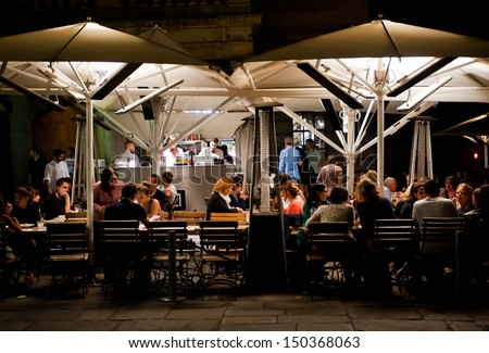 LONDON, UK - AUG 16: People enjoy dinner in a restaurant in Covent Garden in London on August 16, 2013. The Covent Garden area has over 60 restaurants and bars and is a popular night destination