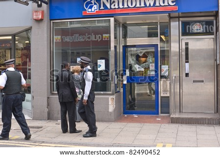 LONDON, UK - AUGUST 9: London Riots. Unidentified members of the public and police outside a branch of Nationwide damaged in the riots. August 9, 2011 in London UK. - stock photo