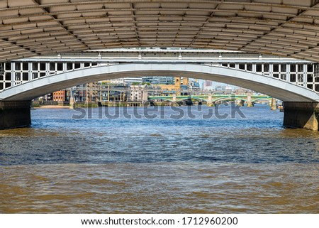 London, UK closeup view under Blackfriars bridge pov from boat on sunny summer day with structure framing city