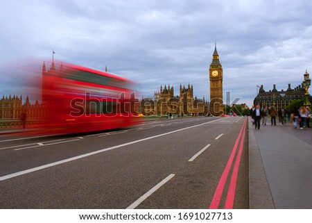 London, UK. Cloudy sky over the city of London, UK. Westminster and Big Ben during the day. Red bus on the bridge, motion blurred people