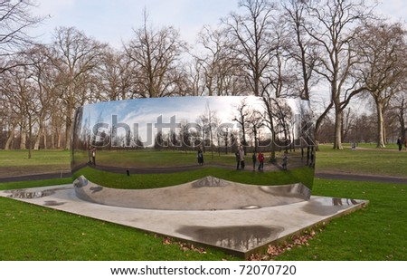 LONDON, UK-FEBRUARY 24:  World Famous Anish Kapoor's Sculpture in Kensington Gardens. The World Turned Upside Down.The Sculpture Reflects the park and People in it. February 24, 2011 in London, UK