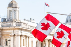 London, UK High Commission of Canada with closeup of row of red Canadian flags on Cockspur Street in Westminster