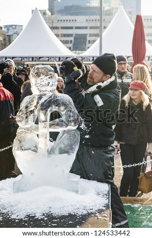LONDON, UK - JANUARY 13: Artists compete in the freestyle category at the London Ice Sculpture Festival, in Canary Wharf. January 13, 2013 in London. - stock photo