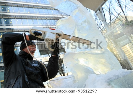 LONDON, UK - JANUARY 13 : Man cuts through ice sculpture with a  chainsaw at the International Ice Sculpting Festival  in London on January 13th, 2012