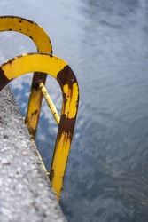 London, UK - July 9 2021: Rusty yellow ladder going into the Blackwall basin's water