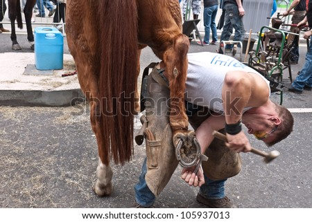 LONDON, UK-JUNE 23: A member of the ancient Worshipful Company of Farriers removes a horse shoe as part of the demonstration of their work, in the street at Cheapside. June 23, 2012 in London UK.