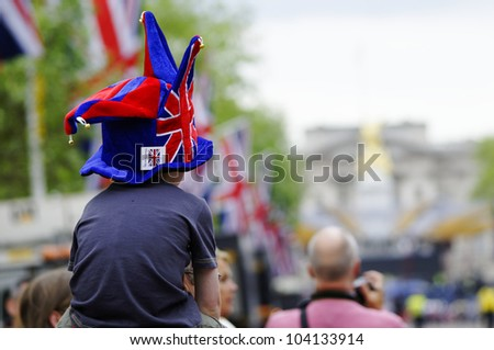 LONDON, UK - JUNE 1: A young spectator looking at Buckingham Palace for the Queen's Diamond Jubilee on June 1, 2012 in London. The main events will take place from June 2 until June 5.