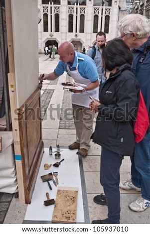 LONDON, UK-JUNE 23: Unidentified visitors watch a member of the Worshipful Company of Painters Stainers demonstrate his work at the Guildhall market, in Celebrate the City. June 23, 2012 in London UK.