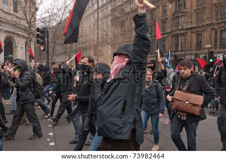 LONDON, UK- MARCH 26: Masked Anarchists march on their way to occupy and protest in central London, during a day of action against government cuts. March 26, 2011 in London, UK.