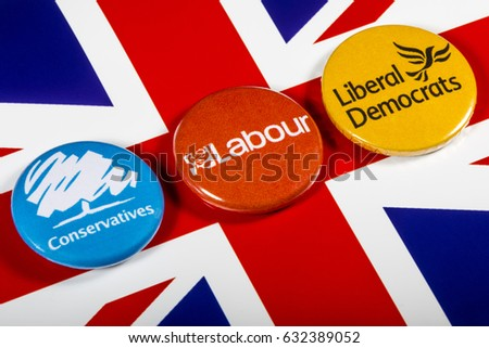 LONDON, UK - MAY 2ND 2017: Conservatives, Labour and Liberal Democrat pin badges over the UK flag, symbolizing the political battle for the General Election, on 2nd May 2017