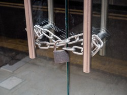 London, UK. May 14th 2020: A retail shop glass front doors, padlocked and chained shut. For security and safety. London lockdown, coronavirus, cover-19 outbreak.