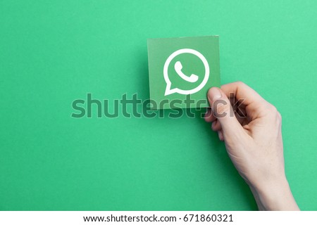 LONDON, UK - May 7th 2017: Hand holding WhatsApp logo. WhatsApp is a popular social media application for sharing messages, images and videos
