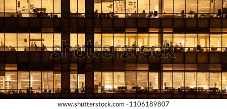 London, UK -  November 1, 2013: panoramic view of a window with people working in the interior of an office building at night. #1106189807
